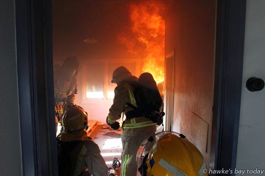 Volunteer firefighters from Taradale and Napier burned a derelict house in Swamp Rd, Puketapu, as a training exercise, setting it alight and extinguishing the fire room by room. photograph