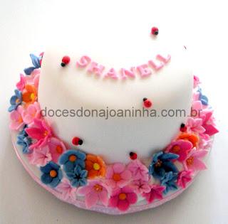 Bolo infantil decorado com flores em tons de pink, rosa, violeta, lilás, joaninhas e o nome da aniversariante.