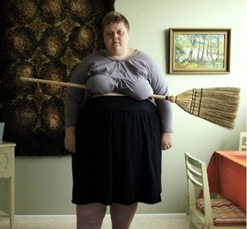 huge woman holds a broom under her boobs