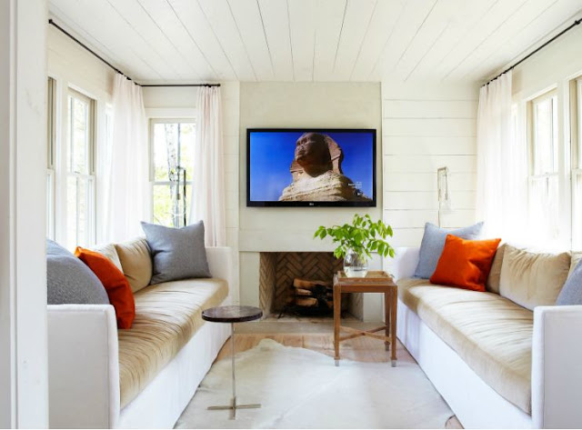 television tv room with dueling two toned sofas, white wood slat ceiling, fireplace, animal skin rug with a wood side table