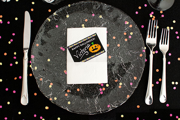 Halloween table with crackled glass plate, silver utensils, and a black place card with a pumpkin illustration tucked into a folded white napkin.