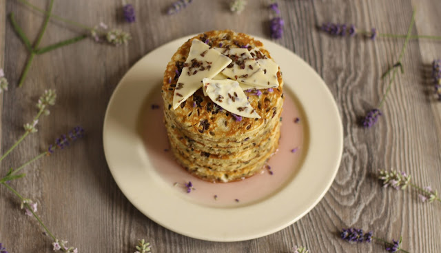 A sweet summery pancake stack with melted white chocolate bits and dried lavender in the batter with some homemade organic lavender syrup and white chocolate bark. Yummy recipe brought to you by the German food blog Pancake Stories. #pancakestories