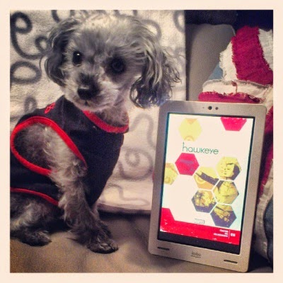 Murchie sits before a white and grey fleece blanket draped over a chair back, my e-reader beside him. Its screen shows the cover for Hawkeye #18, featuring a masked woman visible through a screen of yellow and red honeycombs. Murchie wears a black tank top with red piping. His head is twisted to view something off the left side of the screen.