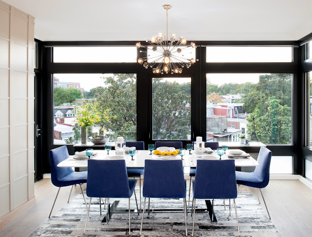 Modern dning room in a Washington DC home by Amy Elbaum with light wood floor, floor to ceiling windows, custom cobalt blue upholstered Pierre Paulin chairs and a modern chandelier