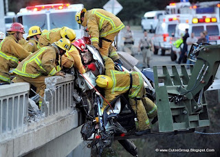 Firefighters rescue a family from a car dangling over a bridge after a fiery crash on Highway 101, California, US.