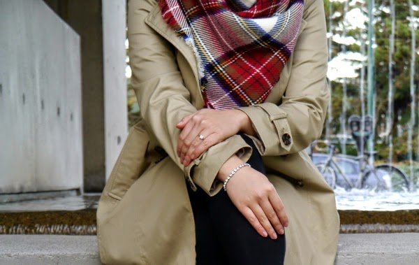 Holiday casual in all black with a classic trench and tartan blanket scarf