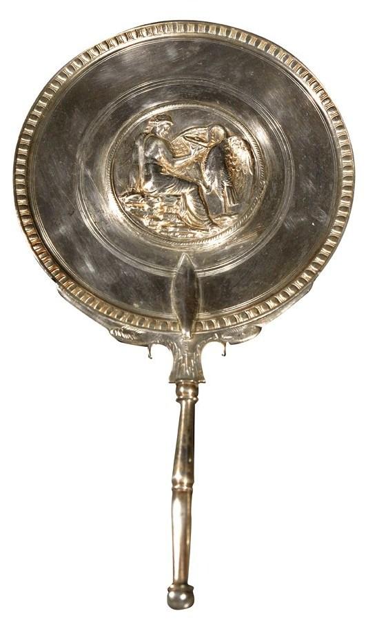 Esta elegante pieza es uno de los pocos objetos de tocador en plata de la colección de Boscoreale. El dorso muestra el mito de Leda seducida por Zeus en forma de cisne.