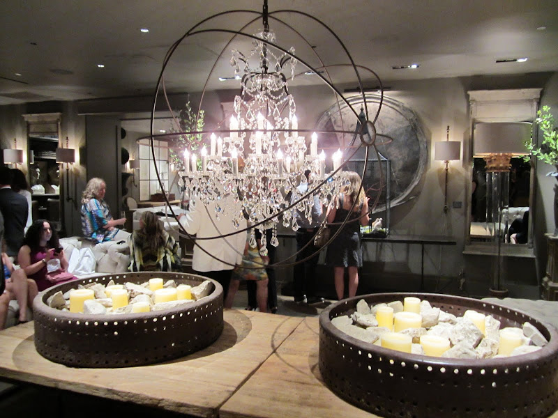 a reclaimed wood table under a crystal chandelier in a wire ball inside the new Restoration Hardware store in Los Angeles