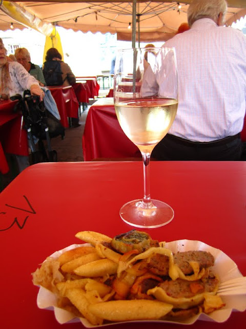 Glass of white wine and a plate of German food in Hamburg, Germany.