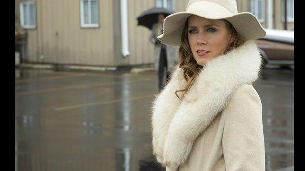 Amy Adams vestida con abrigo camel y 'floopy hat' vintage en American Hustle
