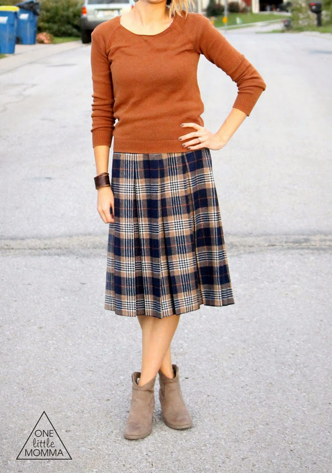 Rust colored sweater, pleated plaid skirt, ankle boots