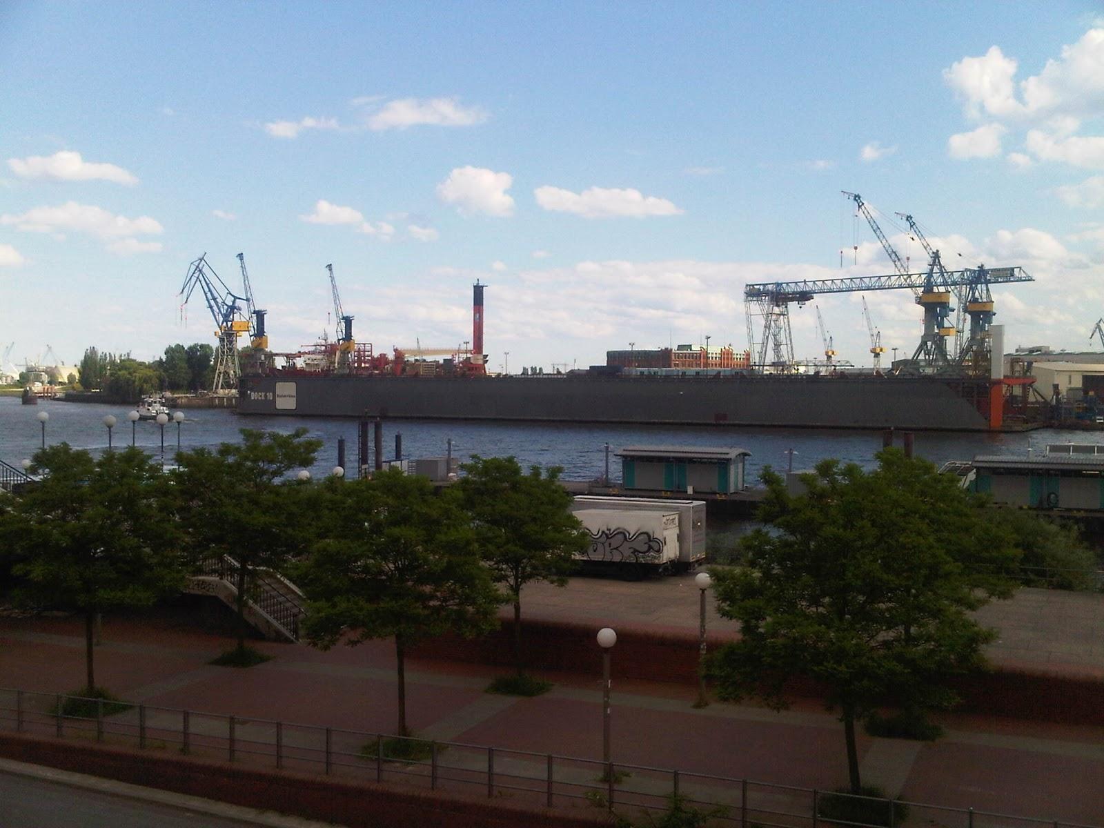 Blick leicht elbaufwärts auf das Dock 10 vom Blohm und Voss. Hafenstraße, Brücke, Wolken, blauer Himmel. Kräne.