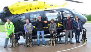 Four german shepherds with their walkers standing in front of the Force helicopter