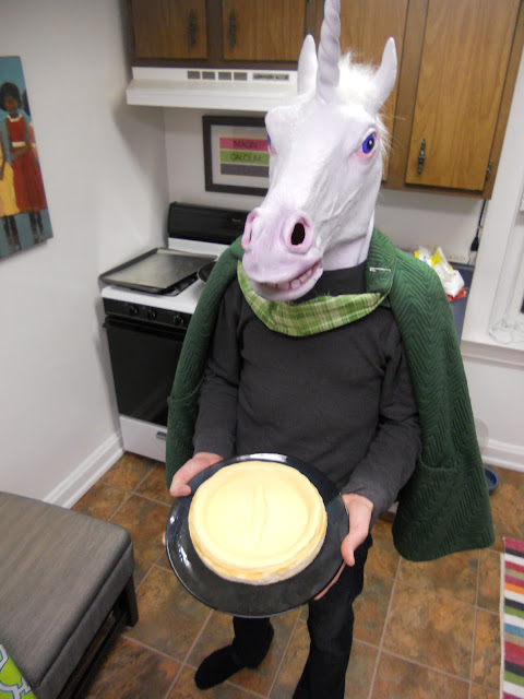 man in unicorn mask proudly displays cheesecake he baked