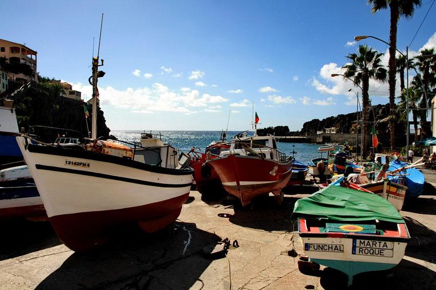 Diversos barcos de pesca, em terra e o mar ao fundo