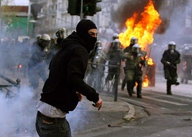 A student who is rioting is chased by riot police.