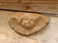 Detall de l'angelet decoratiu de sobre la llinda del portal de la Casa Sastre