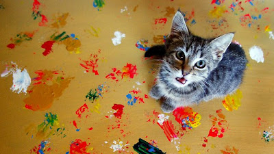 Gatinho pintando quadro com as patinhas