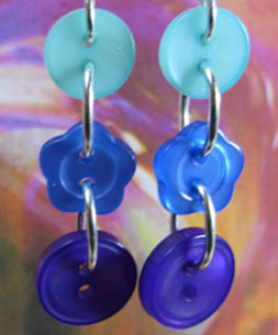 Flattering blue dangle earrings have 3 buttons linked in long strand with silver loops