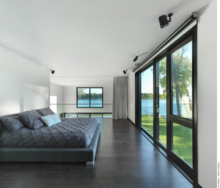 Modern bedroom in Renovated Bord-du-Lac House by Henri Cleinge