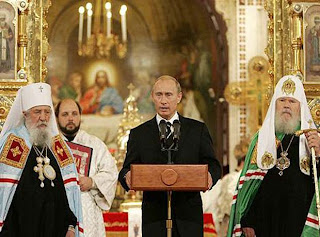 Vladimir Putin standing in front of a bunch of scary looking Russian Orthodox clergy.