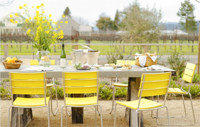Lemon yellow outdoor chairs surrounding a metal picnic table set for lunch al fresco on the edge of a vineyard