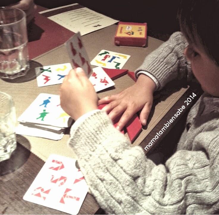 Pequeño divertido en un restaurante jugando al tangram