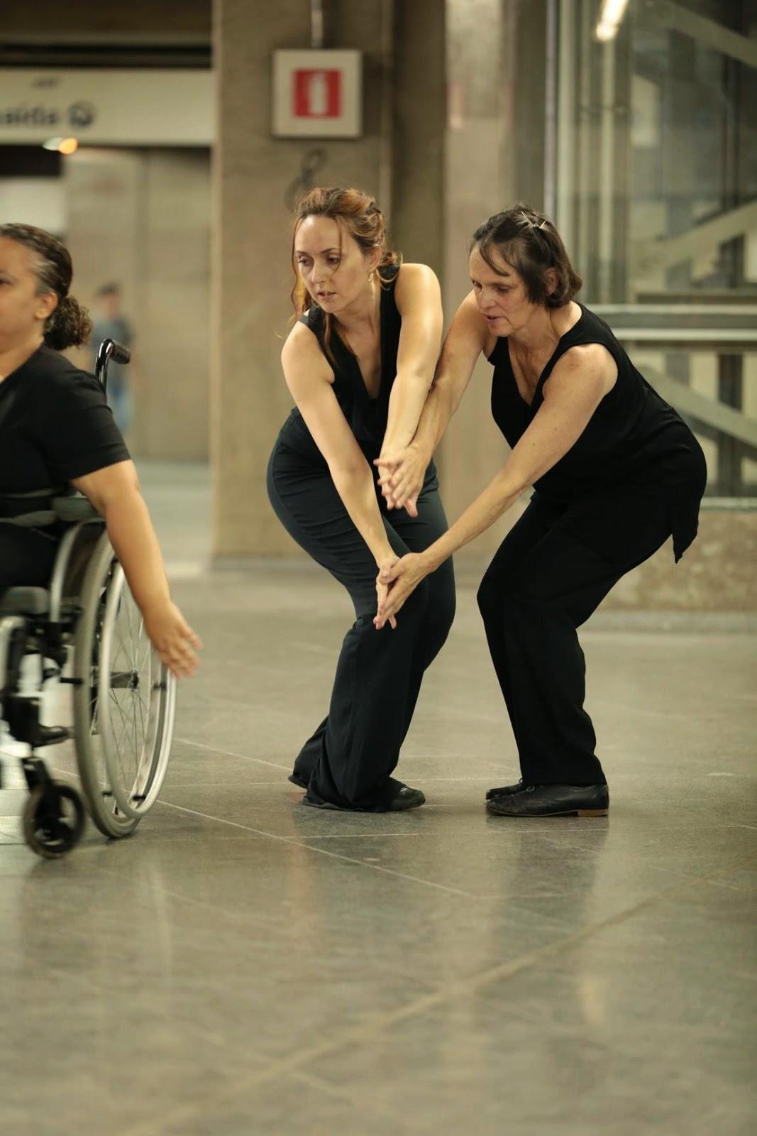 Descrição da Foto: Três intérpretes vestidos de preto dançam na plataforma do metrô. Duas dels estão dançando de pé, com os joelhos semi-flexionados, de frente para a outra, com os braços esticados para o mesmo lado em direção ao chão. Vista parcial de uma intérprete na cadeira de rodas. Placas de sinalização no fundo.