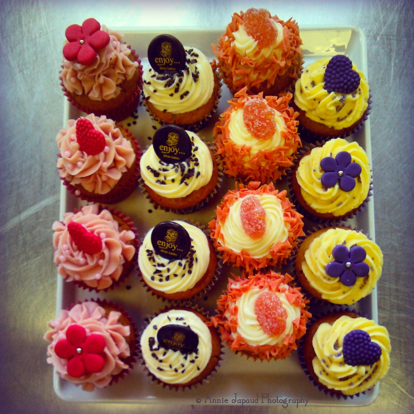 a plate of decorated cupcakes