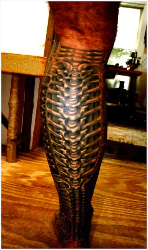 tatuaje en los gemelos estilo alien lleno de texturas y huesos