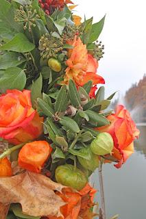 Herbstliche Girlande am Rosenbogen mit Lampionblumen, Eichenlaub, Eicheln und orangen Rosen - Fall wedding ceremony