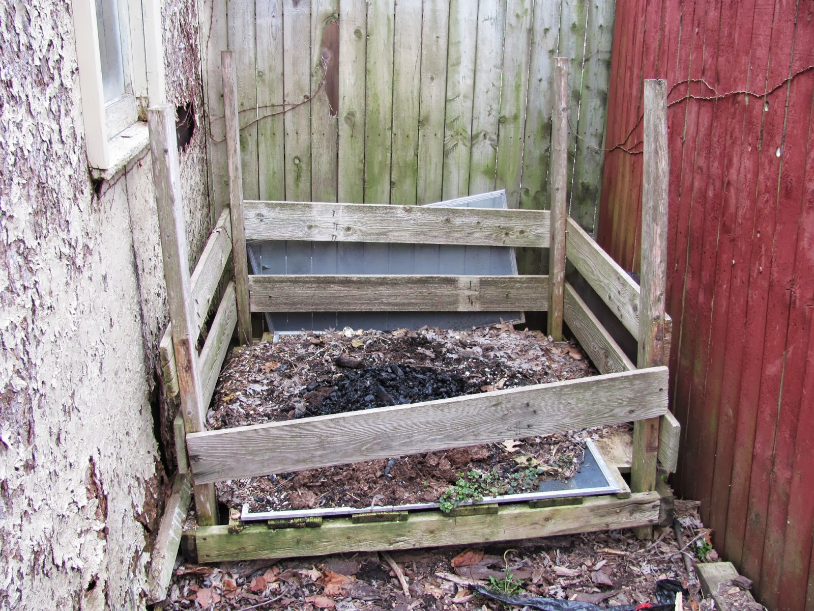 A rickety homemade compost box sits in a gap between a shed and a fence