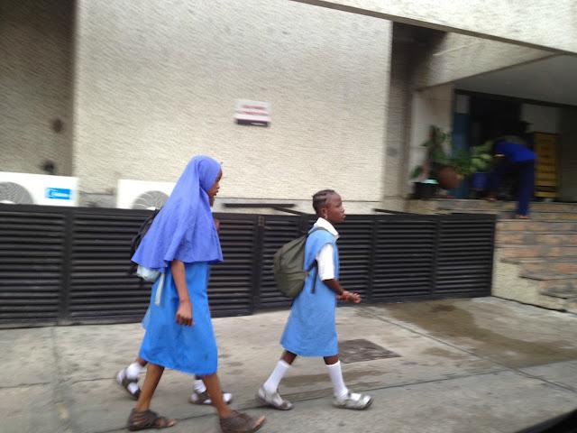 Nigerian children walking to school past an office building