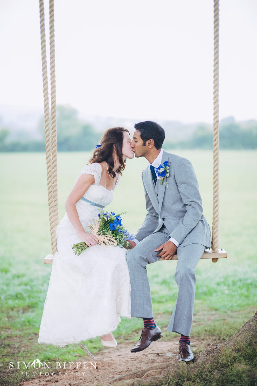Bride and Groom kiss on swing at Quantock Lakes wedding