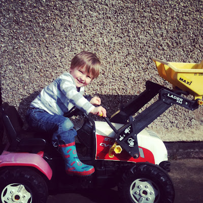 child on toy tractor