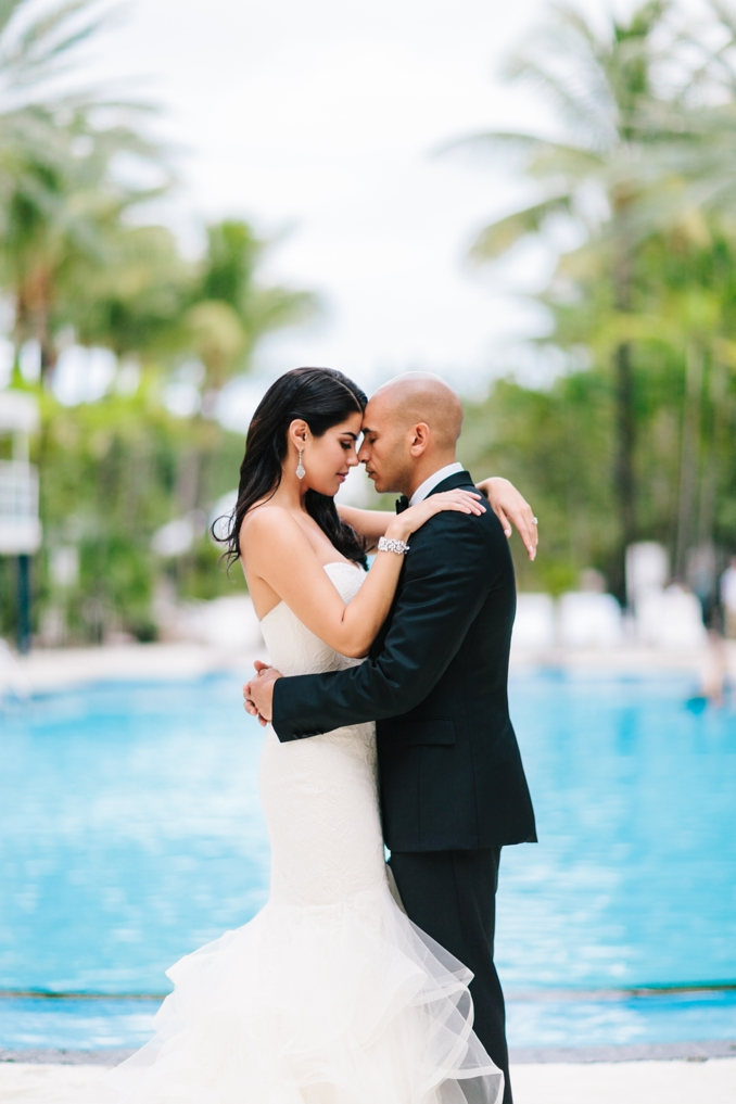 gorgeous portrait of the bride and groom in front of the iconic pool at the raleigh hotel