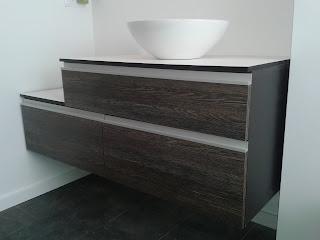 Mueble de aseo con madera de wengué y acero suspendido.