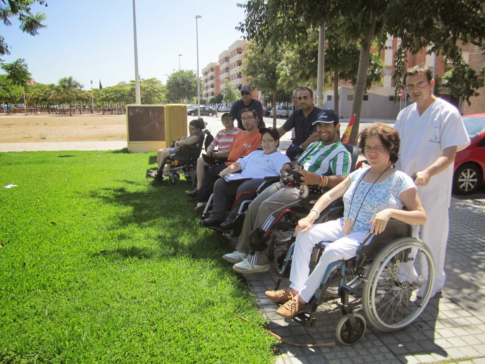 Participantes usuarios de silla de ruedas muestran su imposibilidad de acceder a la zona de césped que forma parte del parque.