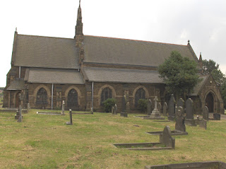 A colour photo of a small church from the north side - there is a chancel and a porch, no tower or spire, but a little bell tower? at the junction of the nave and the chancel roofs. In the foreground is neatly mown grass and a few old gravestones