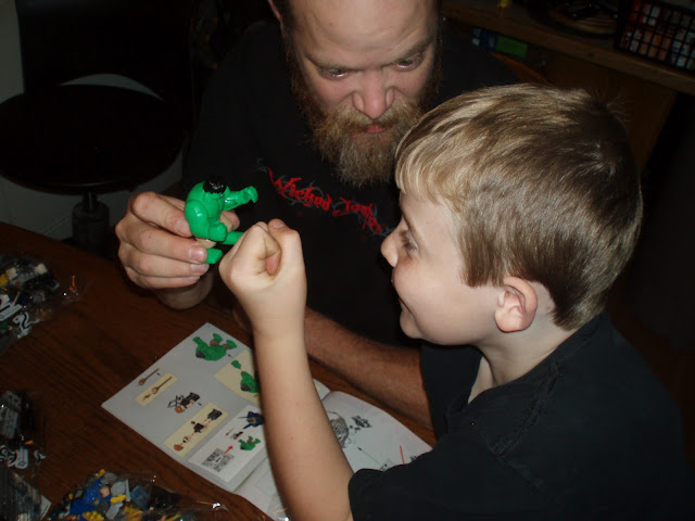 Comic Book Boy playing with Hulk Lego, fist bump