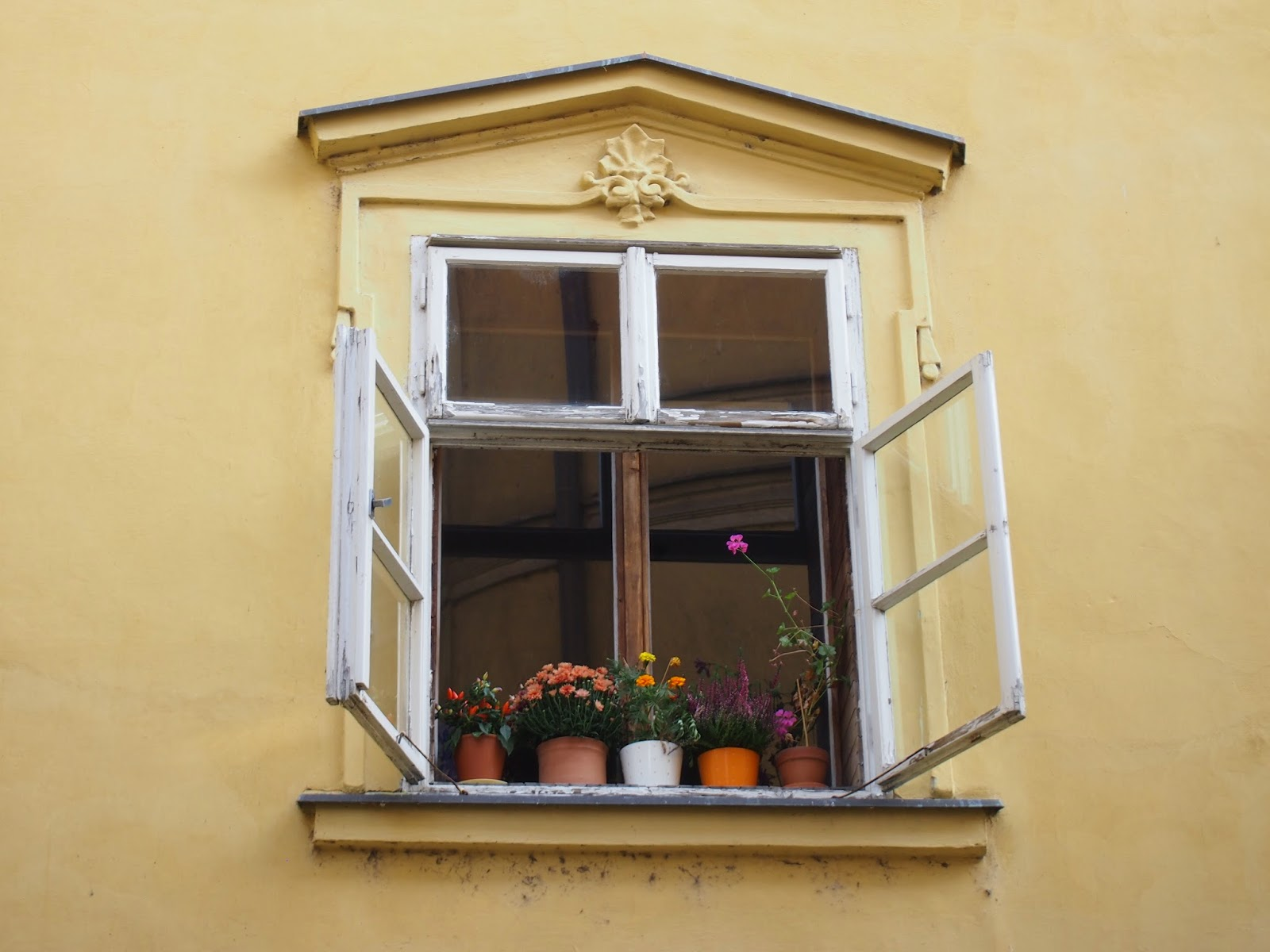 A yellow building with a white window sill with flower pots