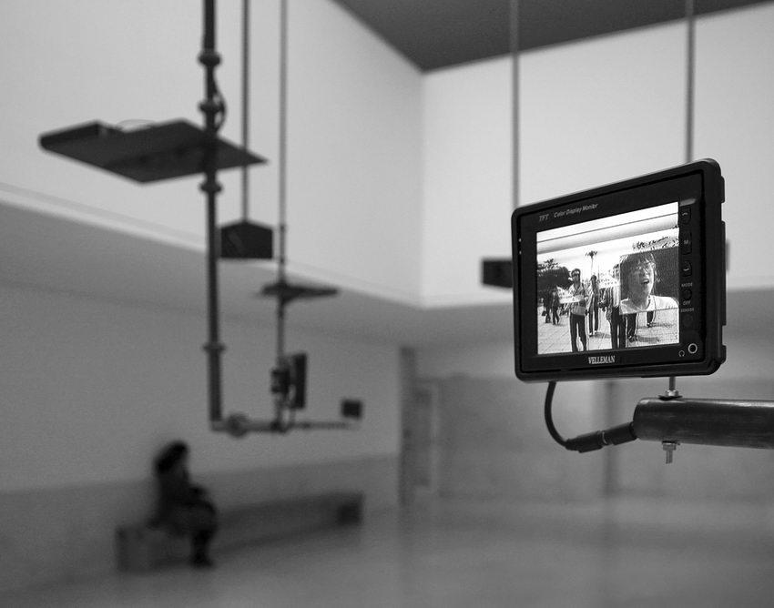 Instalação artística com diverso objectos suspensos do tecto, sendo um deles, um ecrã de video em primeiro plano, onde passa um filme. Todo o resto da foto está ligeiramente desfocado, percebendo-se mrdm assim uma mulher sentada num banco