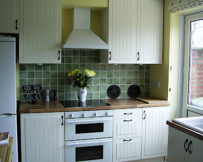 Our white country-style kitchen with walnut laminate worktops and slate-style ceramic floor.