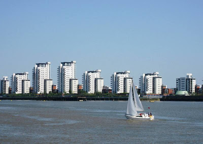 Yacht sailing in front of tower blocks