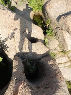 три гранитных колодца в скале расположены рядом, соосно