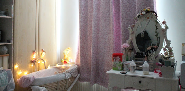 baby's moses basket on stand with fairy lights and black out curtains
