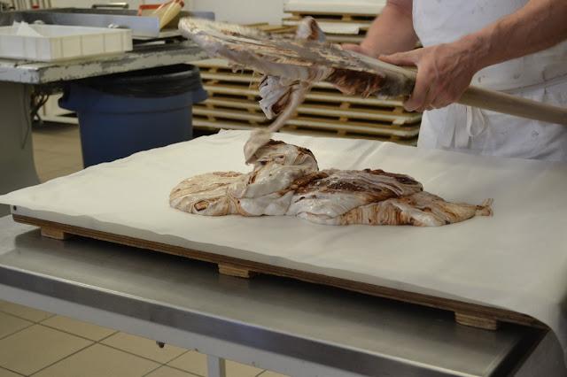De nougat wordt van de grote lepel (lijkt wel roeispaan) op het ouwel geveegd.