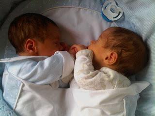 gemelos se dan la mano en la cuna