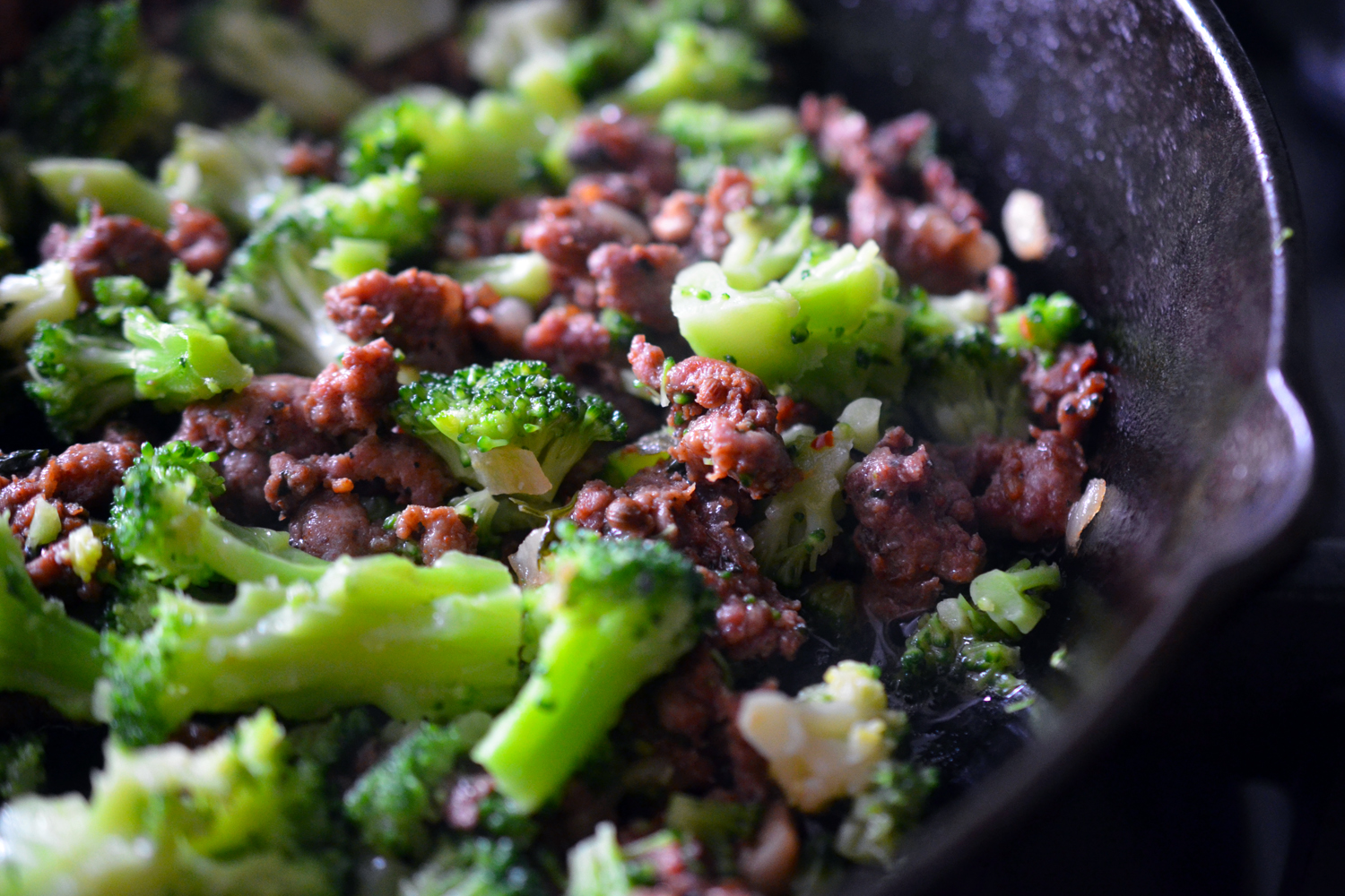 A close up of a cast iron frying pan filled with leftover ground meat and cut up frozen broccoli.