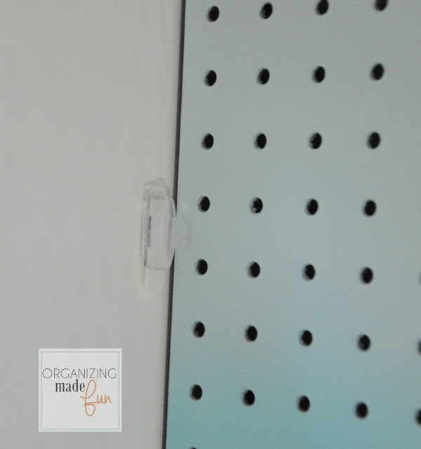 Use light clip with velcro strip to hold back pegboard panel :: OrganizingMadeFun.com